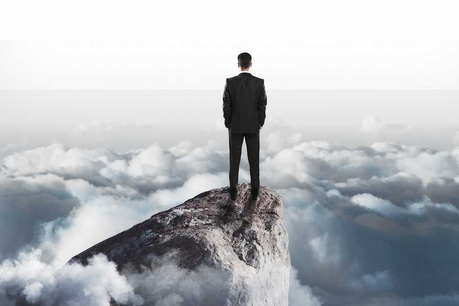 success concept with businessman onn top of rock
